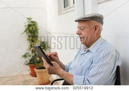 Elderly Man Is Using A Tablet In The Yard Of His House