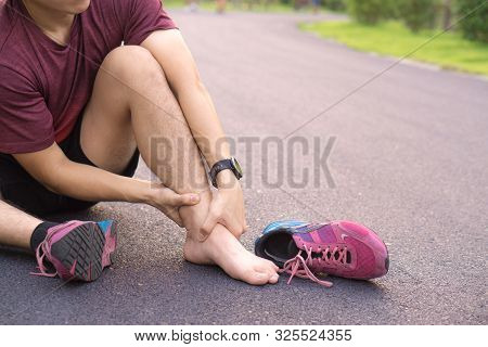 Ankle Sprained. Young Man Suffering From An Ankle Injury While Running At Park. Healthcare And Sport
