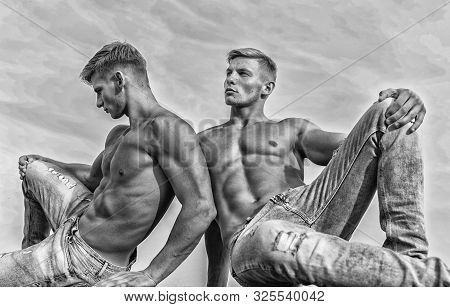 Denim Pants Emphasize Masculinity Sexuality. Men Twins Brothers Muscular Guys Sit Relax Sky Backgrou