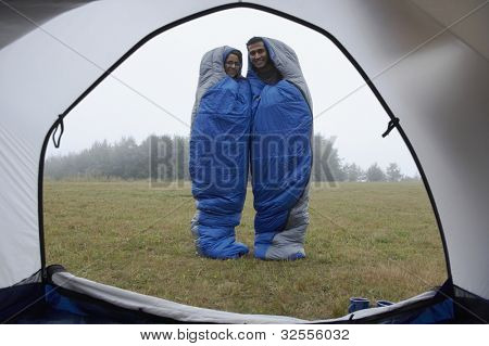 Indian couple wrapped in sleeping bags at campsite