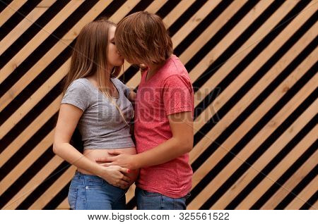 Happy young married couple, husband hugs a beautiful adult pregnant wife. Stand against the background of a striped wall. Second trimester Holds his hands on his stomach poster