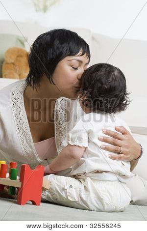 Hispanic mother kissing baby
