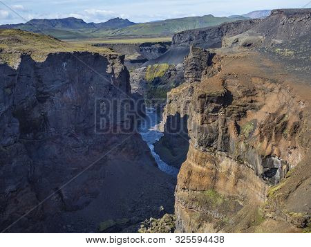 View on majestic Markarfljotsgljufur Canyon gorge and river with green moss covered hills near Botnar camp at Fjallabak Nature Reserve in Highlands of Iceland, blue sky background poster