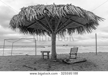 Beach Parasol And Lounge Chair Of A Fishing Town, In Front Of The Ocean, In Black And White. Ayampe
