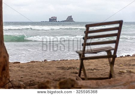Old Wooden Beach Chair Facing The Ocean, On An Overcast And Gloomy Morning, Ayampe, Manabi, Ecuador