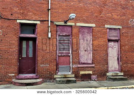 Peeling Red Paint, Missing Slats And Crumbling Concrete On An Old Abandoned Building With Multiple D