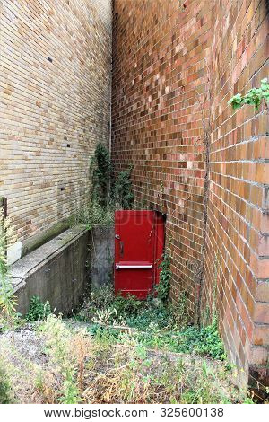 A Bright Red Door Stands Open In The Overgrown Basement Entrance Between Two Buildings In A Small To