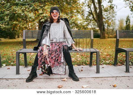 Smiling Middle-aged Female Dressed Boho Fashion Style Colorful Long Dress With Black Leather Biker J