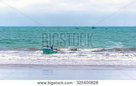 Fishermen In A Small Boat In The Ocean Coming Back To Land, Puerto Cayo, Manabi, Ecuador