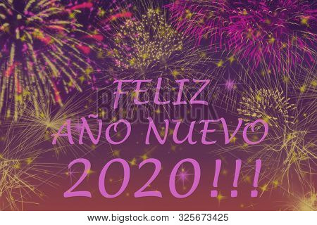 New Year 2020 Greetings Card. Fireworks Effects On A Colorful Background.