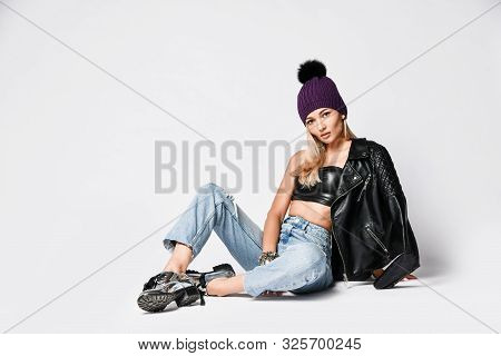 Glamour Biker Style Blonde Woman In Torn Jeans, Leather Top And Jacket With Zippers, Winter Hat And