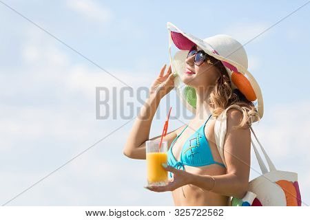 The Girl Lies On The Beach With A Glass Of Juice. A Cute Woman Of 30-35 Years Old In A Blue Bikini W