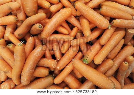 Background Of Fresh Carrot On The Market Stall. Healthy Ripe Carrot For Preparing Meal. Organic Food