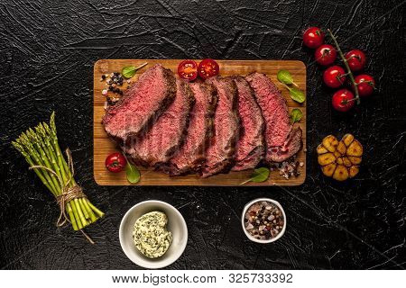 Roast Beef. A Large Piece Of Meat With Fresh Vegetables Is Cut On A Board And Ready To Eat. Black Ba