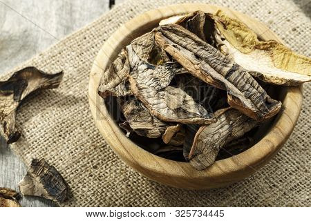 Choped Dried Cepes Mushrooms On Burlap, On A Brown Wooden Background