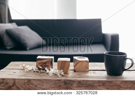 Spring home decor on rustic coffee table over black sofa with cushions. Grey vases and spring flowers on wooden bench in small dark room interior. Scandinavian home style.