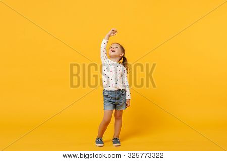 Little Cute Child Kid Baby Girl 4-5 Years Old Wearing Light Denim Clothes Isolated On Pastel Yellow