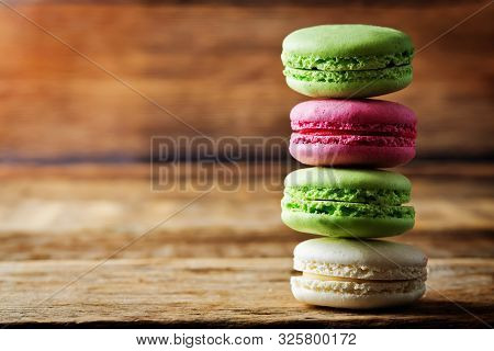 Multicoloured Macarons On A Dark Wood Background