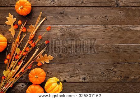Autumn Side Border Of Pumpkins, Leaves And Chinese Lantern Branch. Top View Against A Rustic Wood Ba