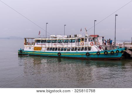 Si Racha, Thailand - March 16, 2019: Blue White Sichang Ferry Boat Docked At Ko Loi Pier Under Silve