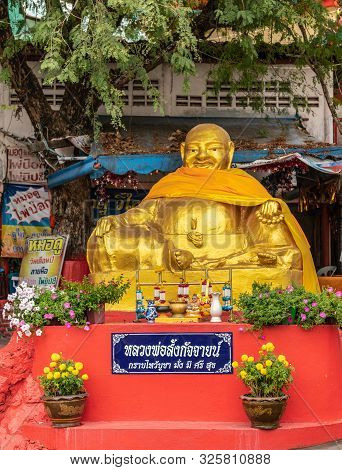 Si Racha, Thailand - March 16, 2019: Golden Obese Sitting Buddha Statue On Red Pedestal Down From Wa