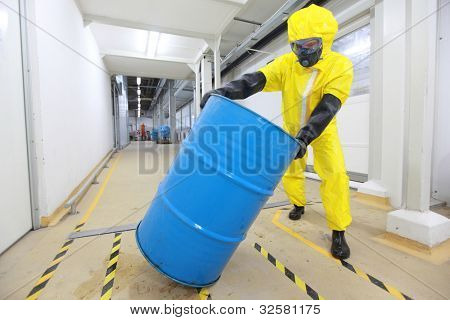 Worker in protective uniform,mask,gloves and boots rolling barrel of chemicals