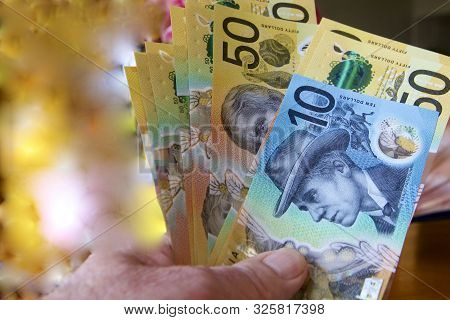 Australian Dollars Being Offered By Hand For Payment.