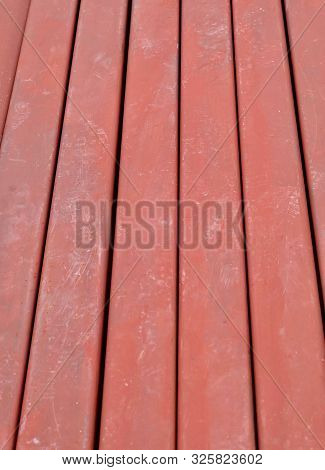 Textured Background Of C Shaped Metal Bar On A Ground In Construction Site.