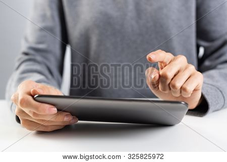 Businesswoman Using Tablet Computer For News Read. Close-up Of Female Hands Holding Tablet Device At