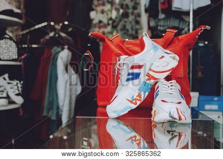 Fast Fashion Concept. Red Handbag And Shoes On  Shelf In Shop, Store. Lots Of Clothes In The Store.