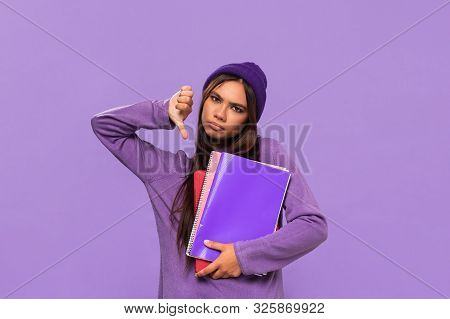 Sad African-american Teenager In A Hat And Sweater Holding Folders And Showing Thumb Down Standing I