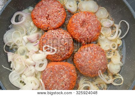 Raw Uncooked Burgers With Caramelising Onions Cooking In A Deep Fry Pan Top View