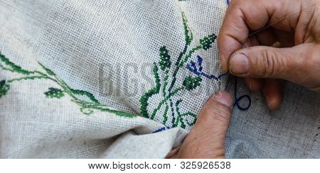 Hands Of An Elderly Woman Embroidering A Cross-stitch Floral Pattern On Linen Fabric. Embroidery, Ha