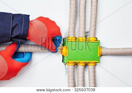 An Electrician Connects An Electric Conduit To A Square-shaped Distribution Box Made Of Green Plasti