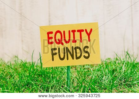 Writing note showing Equity Funds. Business photo showcasing type of mutual fund that buys ownership in businesses Plain paper attached to stick and placed in the grassy land. poster
