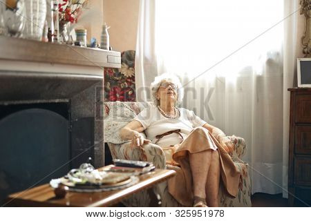 elderly woman sleeps on an armchair