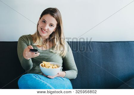 Beautiful Woman Sitting On Sofa And Watching Tv