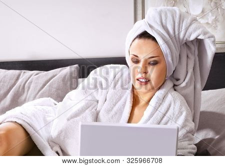 Rich woman in white bathrobe on a bed with laptop