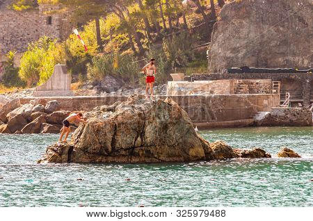 Monterosso Al Mare, Italy - September 02, 2019: A Man, Tourist With Red Swimming Shorts Standing On