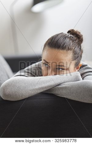Stressed Young Housewife In Living Room. Despair And Depression Concepts