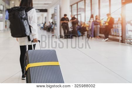 Young Woman Pulling Suitcase In Airport Terminal. Young Woman Traveler In International Airport With