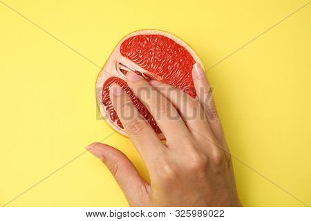 Young Woman Touching Half Of Grapefruit On Yellow Background, Top View. Sex Concept