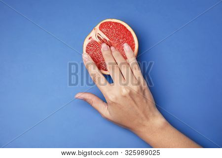 Young Woman Touching Half Of Grapefruit On Blue Background, Top View. Sex Concept