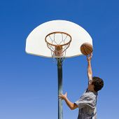 A teen boy jumps and shoots a basketball poster