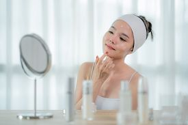 Portrait Of Beautiful Asian Young Woman Caring Of Her Skin Sitting Near Mirror In Bedroom With Skin