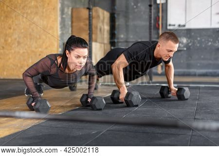 Attractive Sports People Are Working Out With Dumbbells In Gym. Healthy Lifestyle Concept.