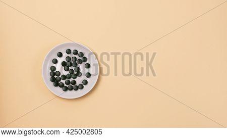 Green Spirulina Pills On The Plate Top View Super Food Concept Spirulina Dietary Supplement Yellow B