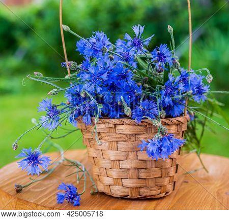 A Bouquet Of Cornflowers In A Wicker Basket On A Wooden Background. Blooming, Flower Bouquets.