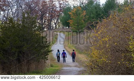 Friends Hiking In The Forest Footpath With Social Distancing.