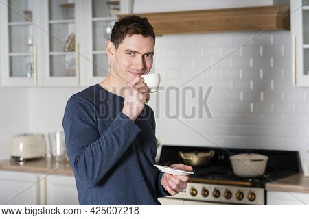 Portrait Of Handsome Happy Guy, Young European Man Drinking Coffee Or Tea From Mug, White Cup In Ear